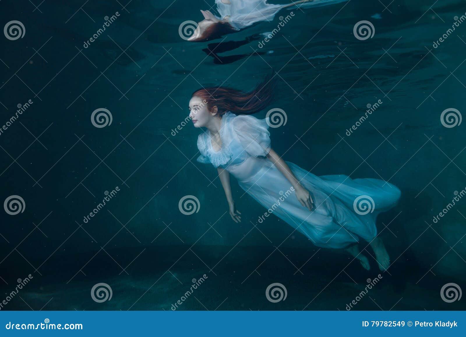 Feevrouw in witte kleding onderwater