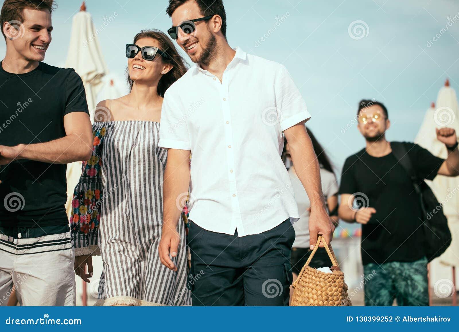 Feiertage, Ferien Gruppe Freunde, die Spaß auf Strand, dem Gehen, Getränkbier, dem Lächeln und dem Umarmen haben