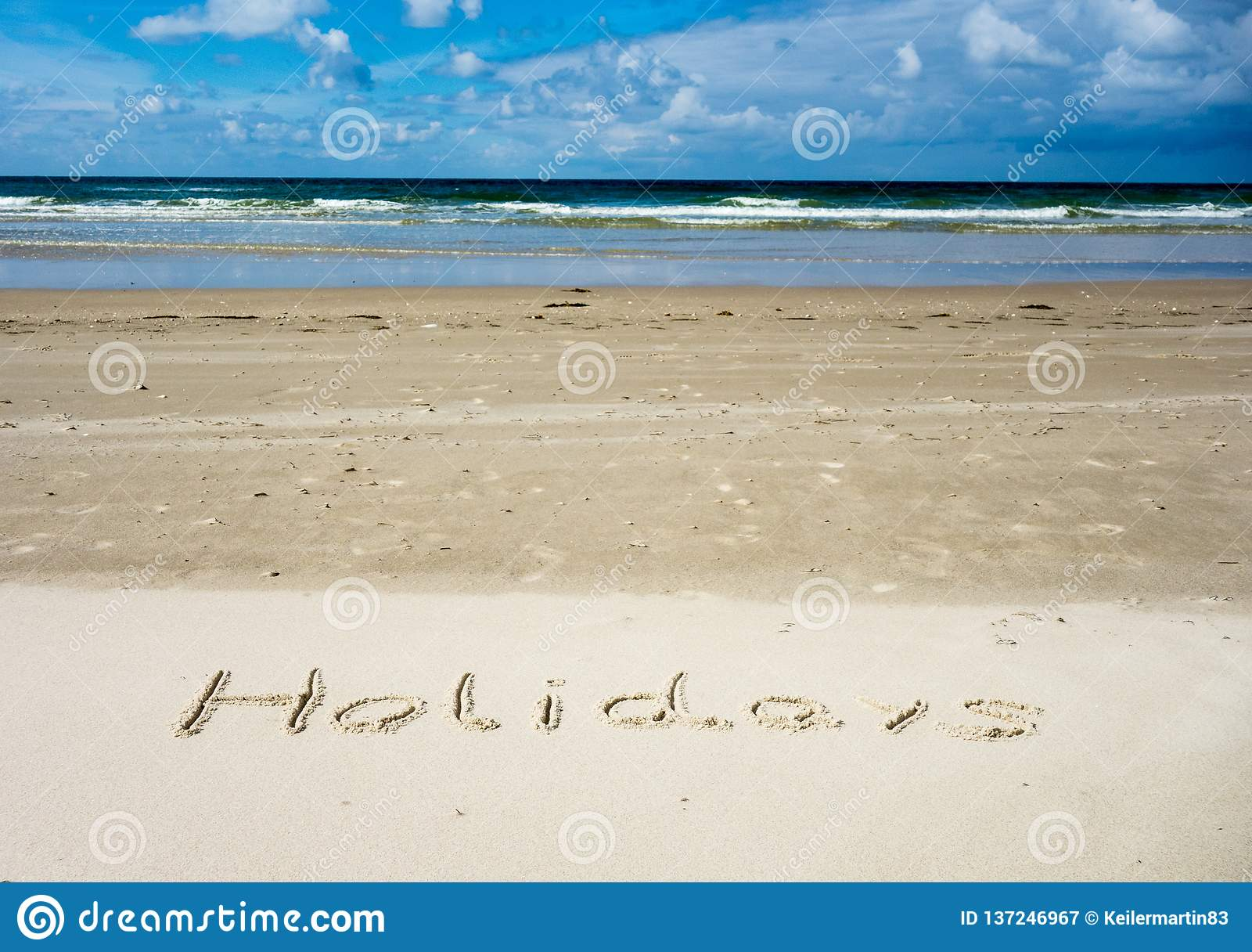 Feiertage geschrieben in Sand mit Meer im Hintergrund und im blauen Himmel