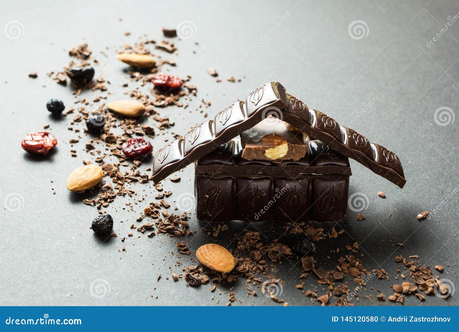 Feiertagsschokoladenhaus und -Trockenfrüchte mit Nüssen auf einem schwarzen Hintergrund
