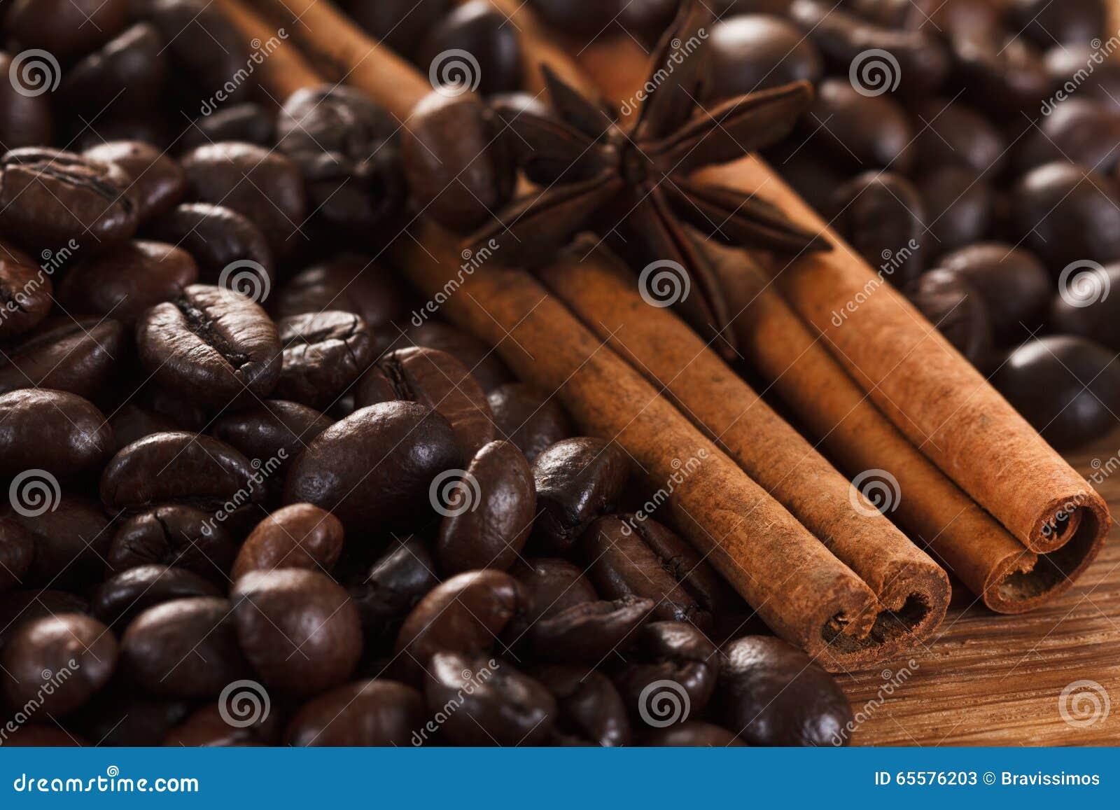 Feijões de café com canela e anis na tabela de madeira