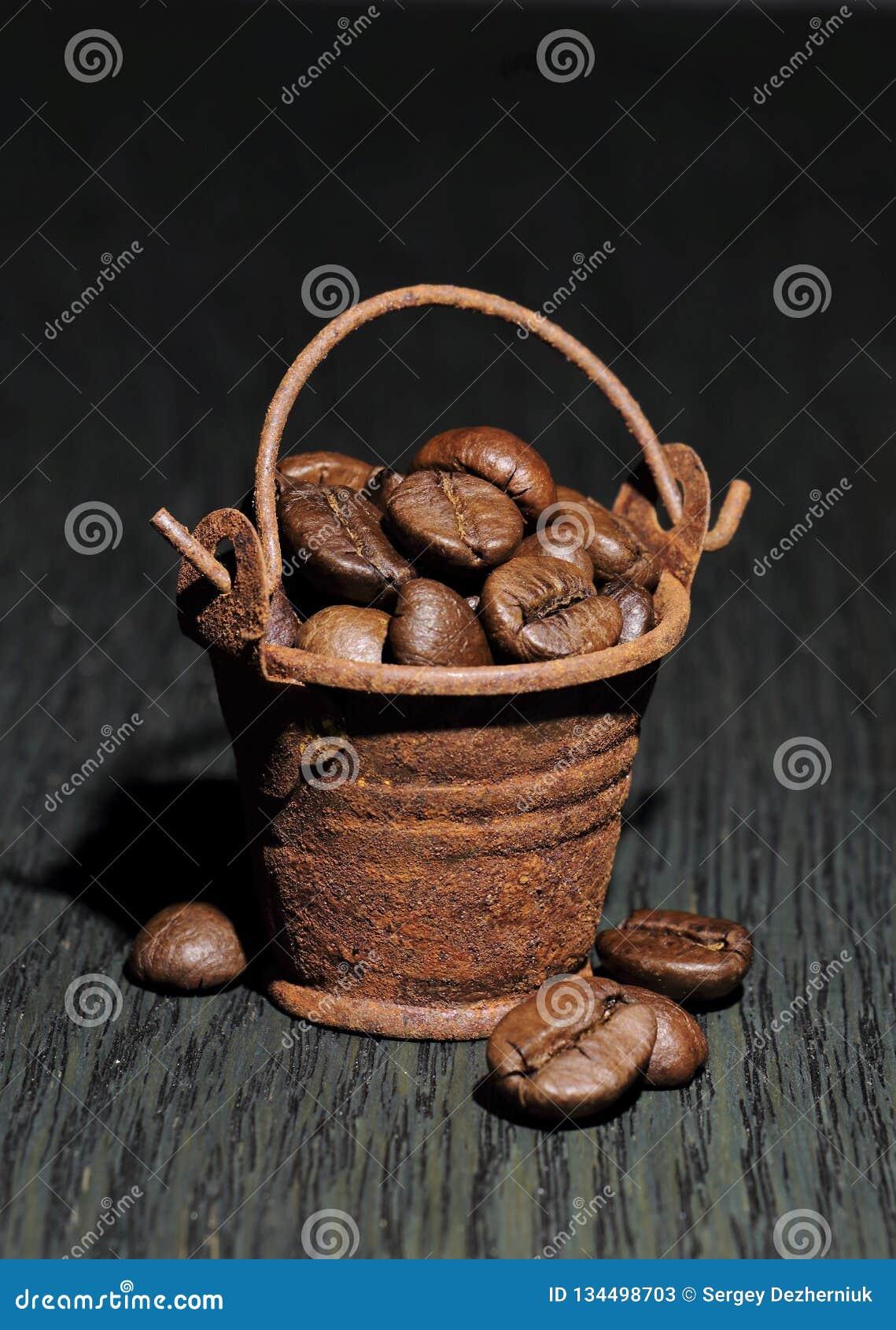 Feijões de café em uma cubeta oxidada pequena em um backgroun escuro