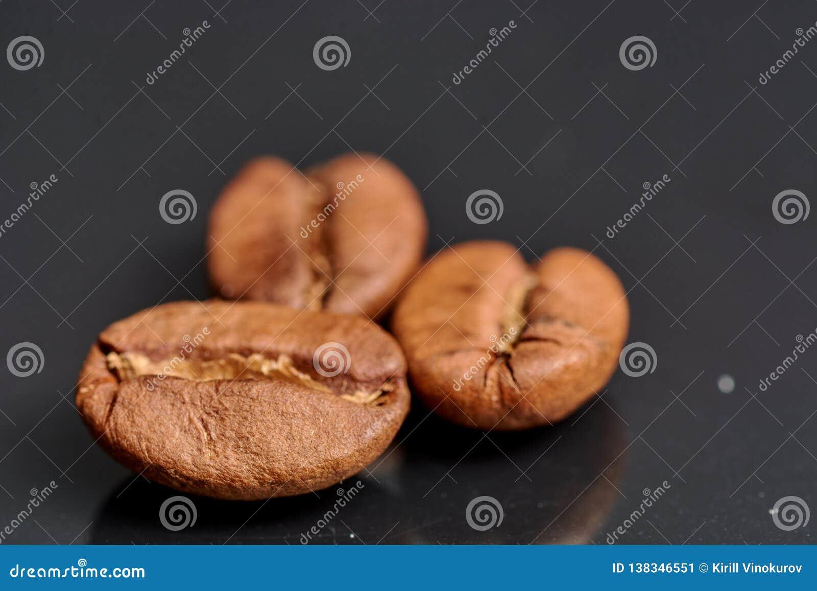 Feijões de café no fundo preto consistente com