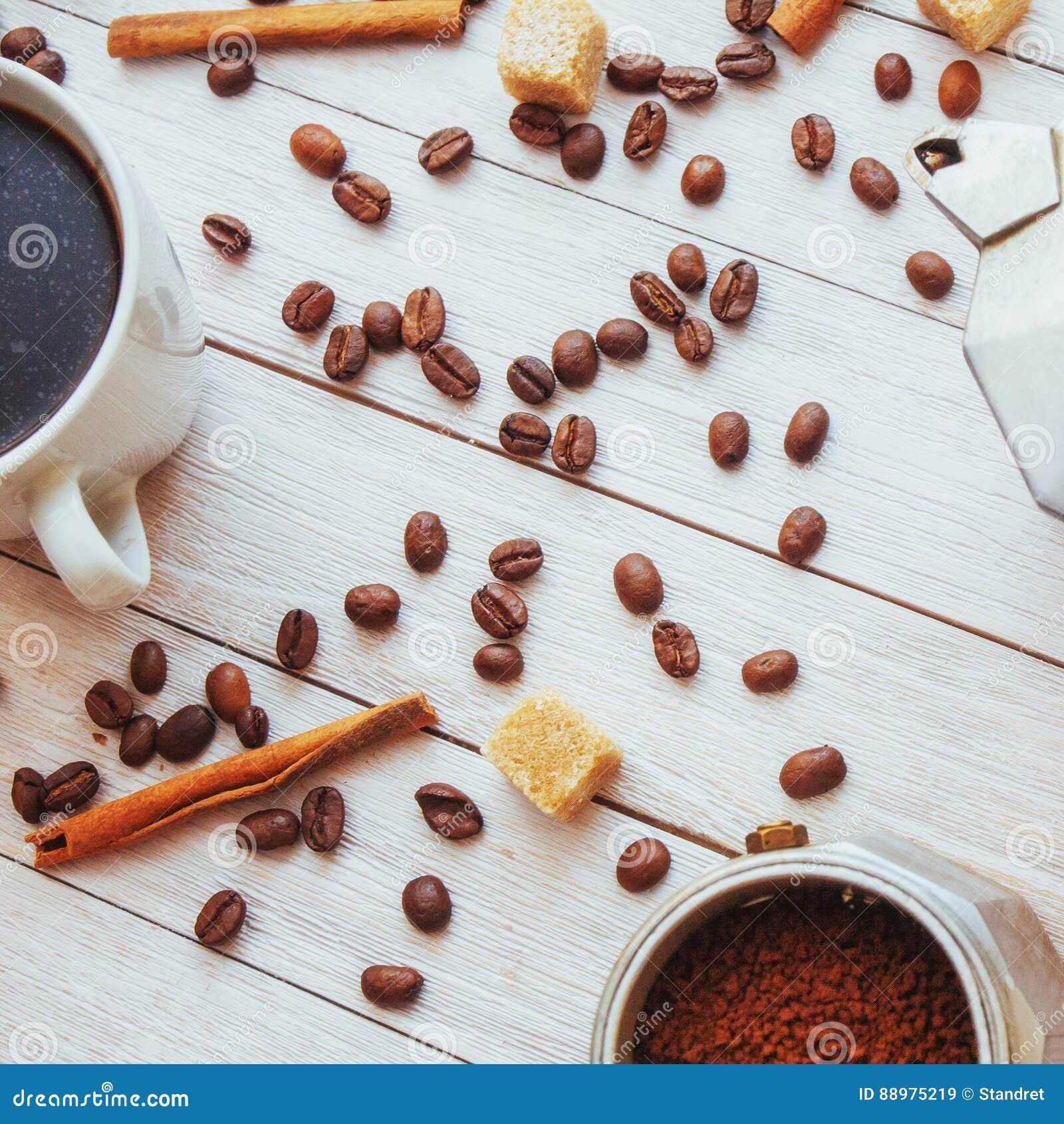 Feijões e xícara de café de café na tabela no fundo
