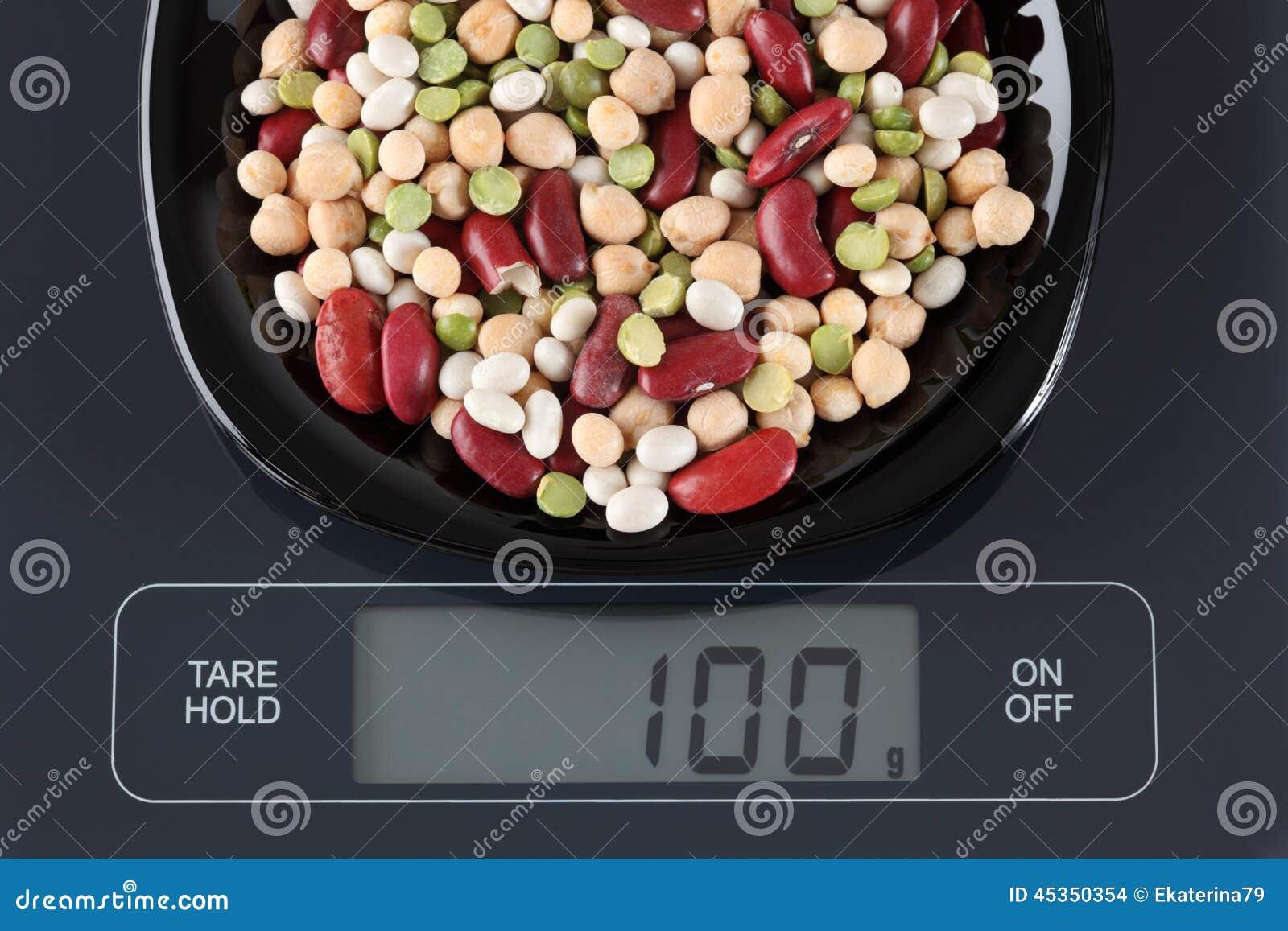 Feijões misturados da leguminosa na escala da cozinha