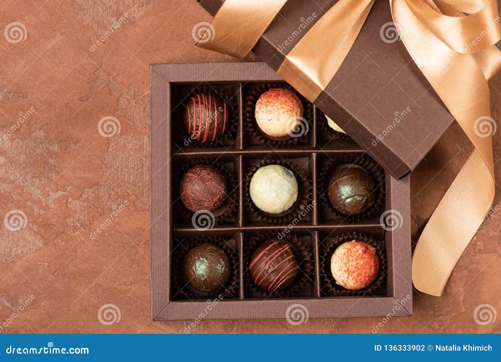 Feine Schokoladen im Handwerkskasten mit Satinband auf einem dunklen Hintergrund Flacher Plan Festliches Konzept Kopieren Sie Pla