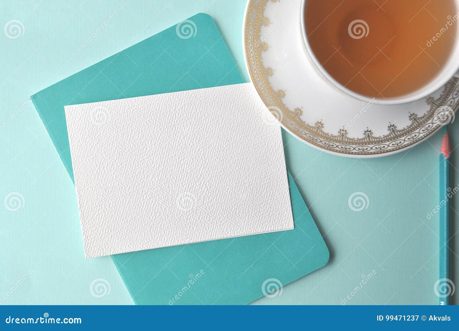 Feine weiße Porzellanporzellanschale mit Tee, Knickentenbleistift, weißer Anmerkungskarte und tadellosem blauem Hintergrund des A