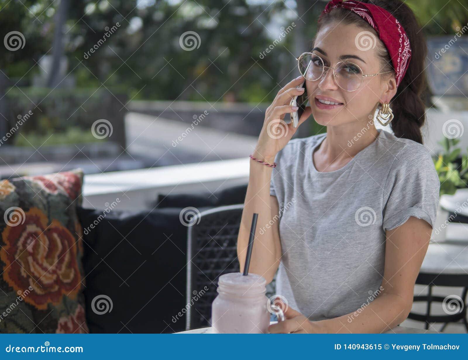Feines erwachsenes Mädchen mit weißem Telefon in ihrer Hand, sitzend im offenen exotischen Café,