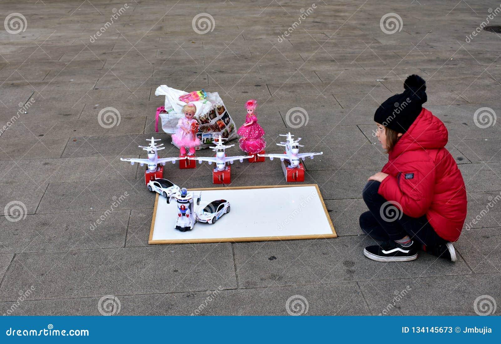 Feira do Natal da cidade Uma menina com um revestimento vermelho e um chapéu negro olha os brinquedos no La Coruna da rua, Espanh
