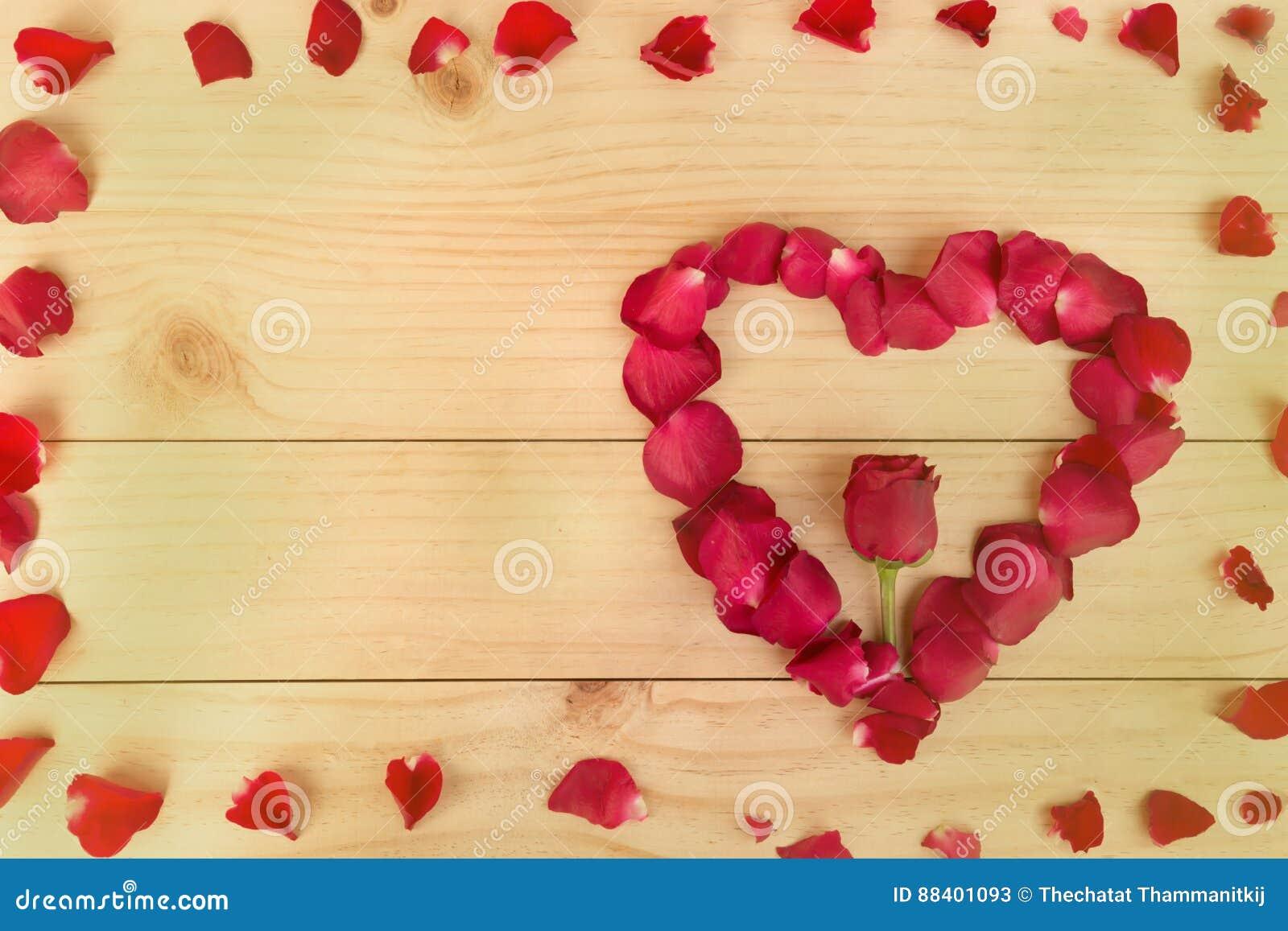 Feld, Herzform gemacht aus rosafarbenen Blumenblättern heraus auf hölzernem Hintergrund, VA