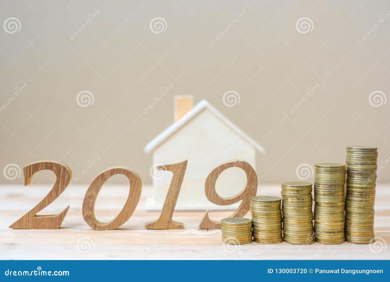 2019 Felices Año Nuevo con la pila de las monedas de oro y número de madera en la tabla negocio, inversión, planificación de la j