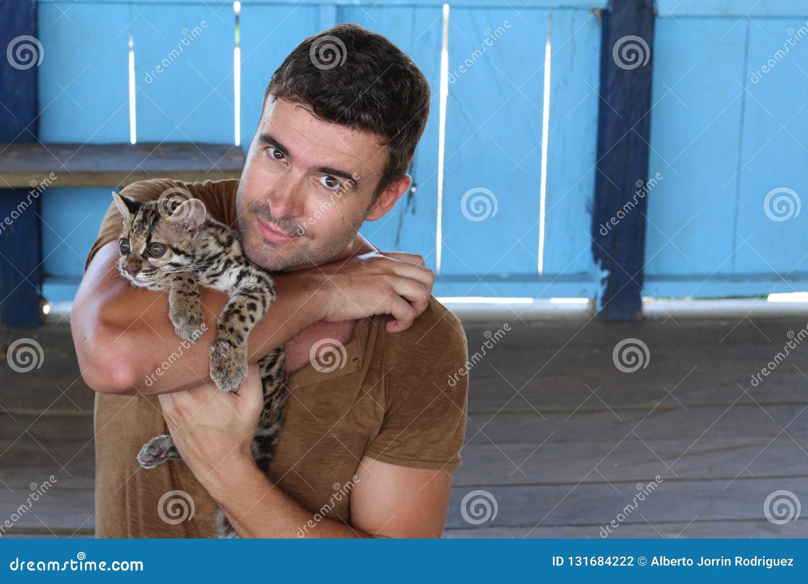 Felino salvaje del hombre del bebé blando de la tenencia