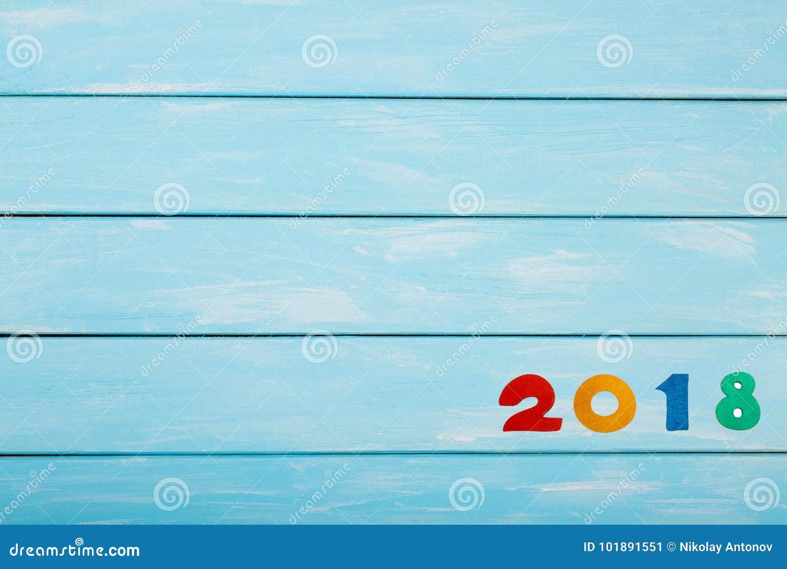 Feliz Año Nuevo 2018 de figuras de madera reales en fondo de madera azul en colores pastel Plantilla agradable para su proyecto d
