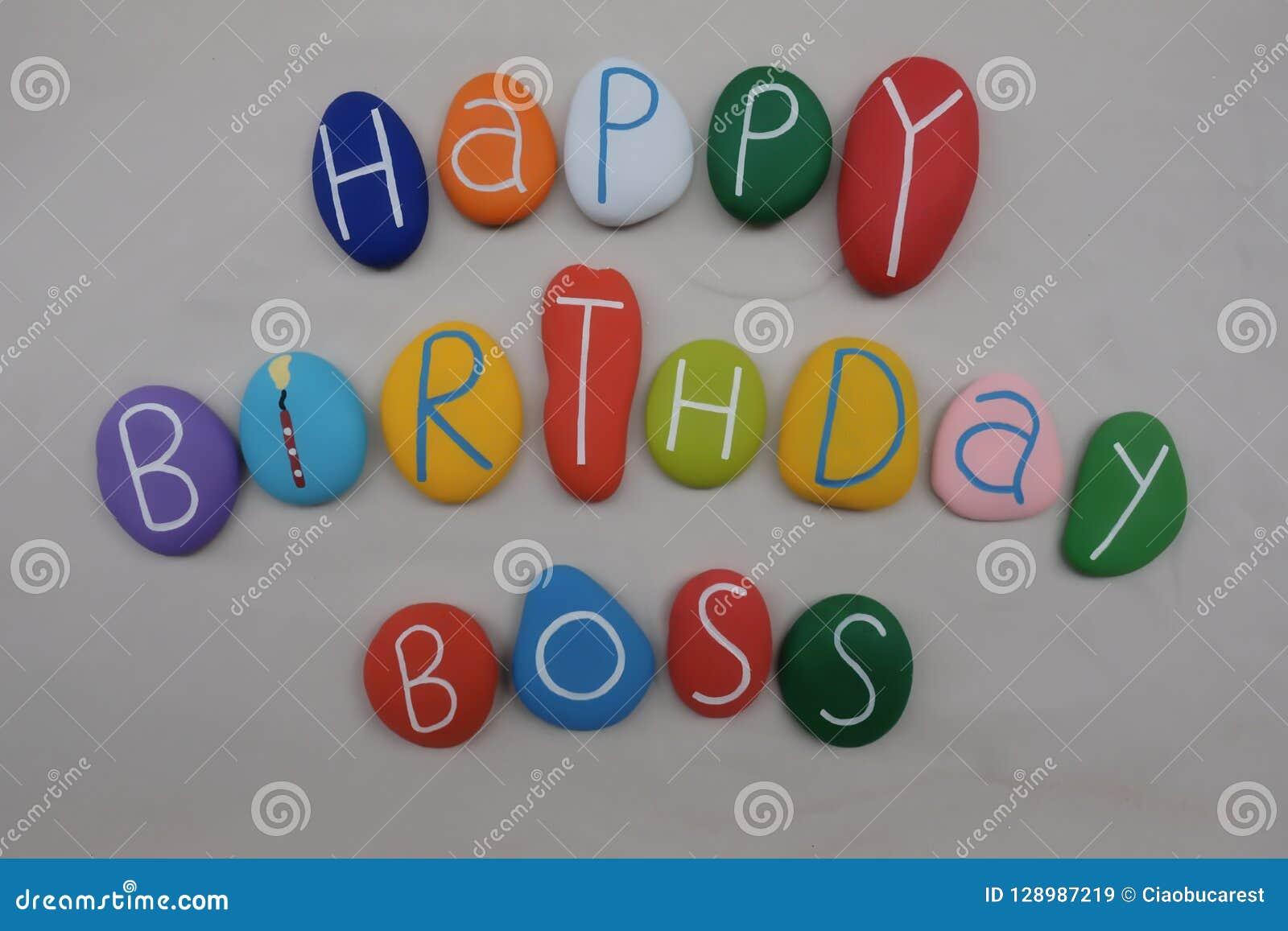 Feliz cumpleaños Boss con las piedras coloreadas sobre la arena blanca