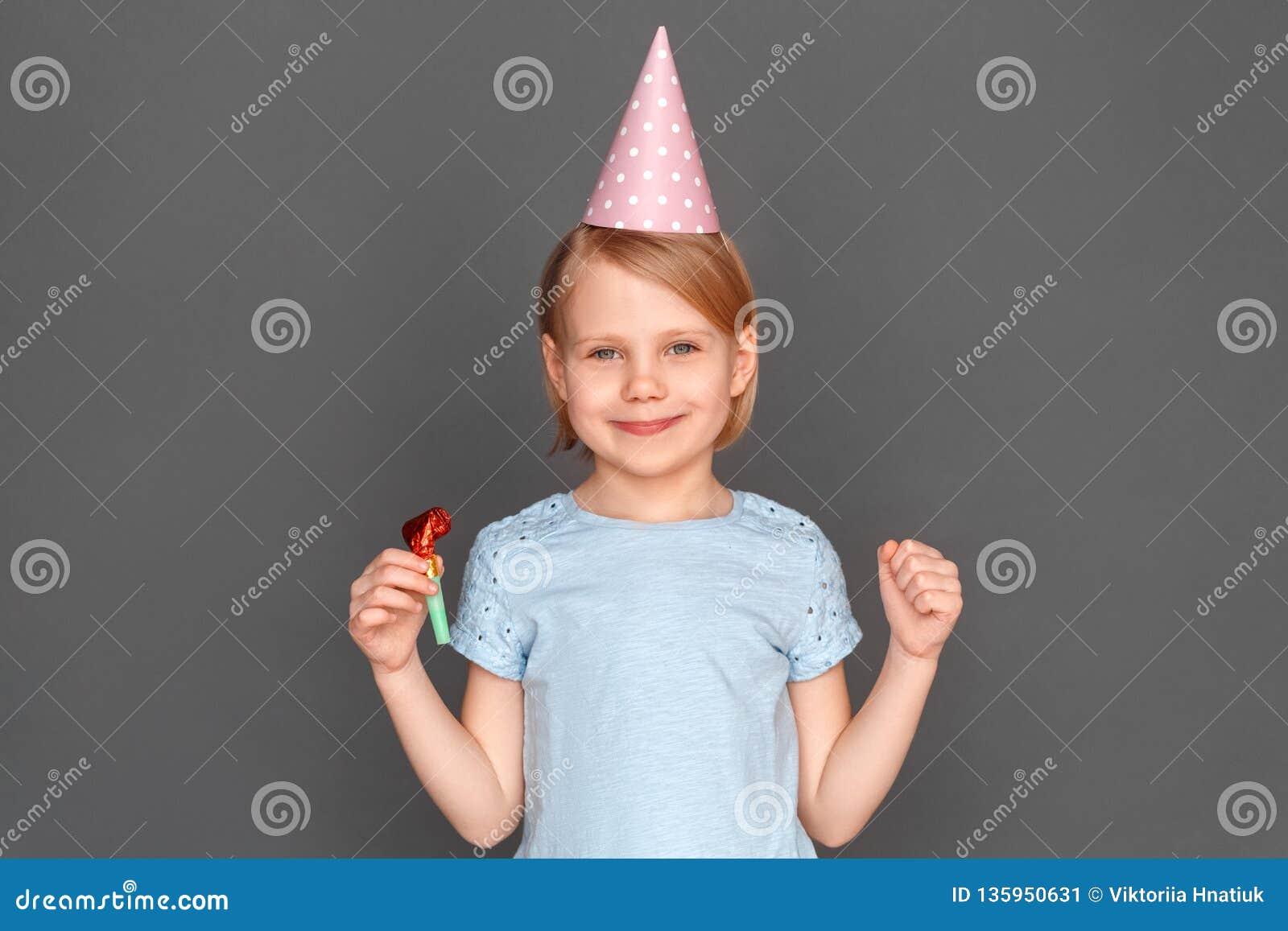 Feliz cumpleaños Casquillo que lleva de la niña aislado en gris con la sonrisa del cuerno del partido