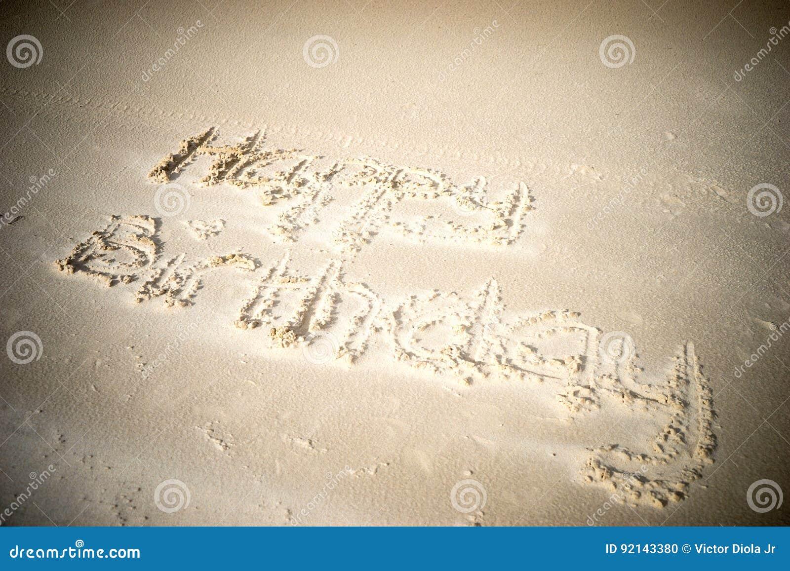 Feliz cumpleaños escrito en arena