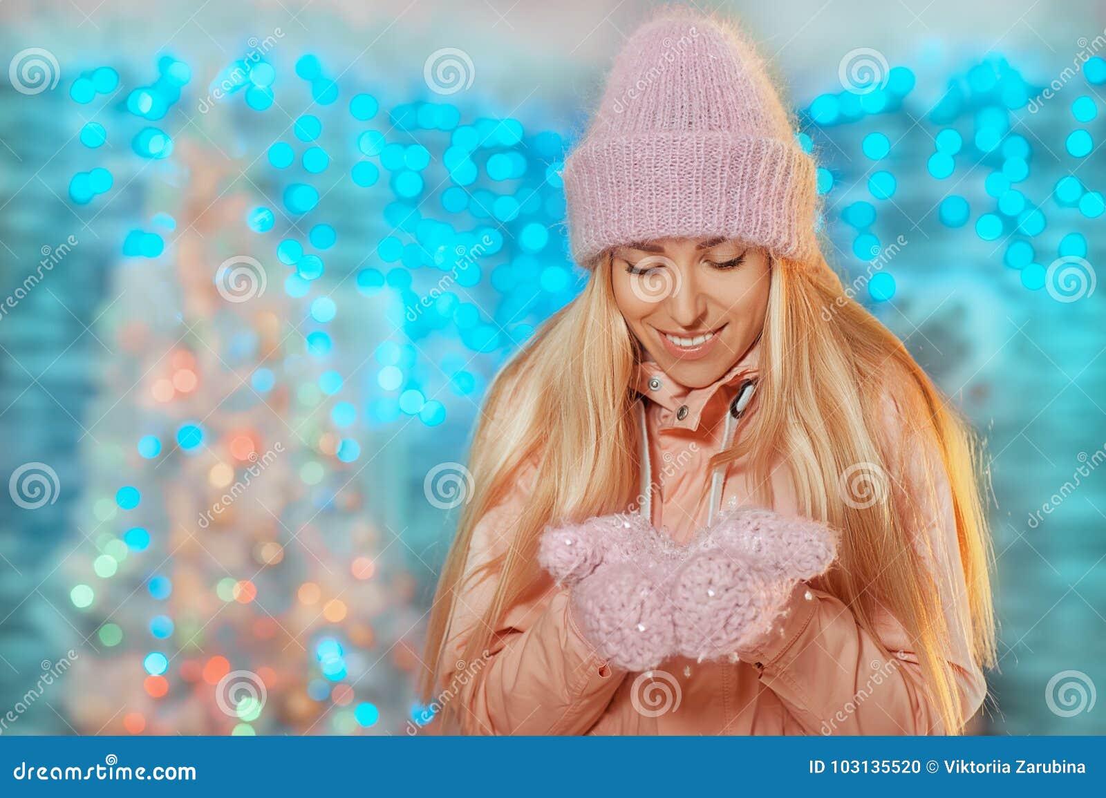 Feliz Natal e ano novo feliz! menina de sorriso bonita feliz no chapéu e em mitenes feitos malha que fica exterior e que guarda a
