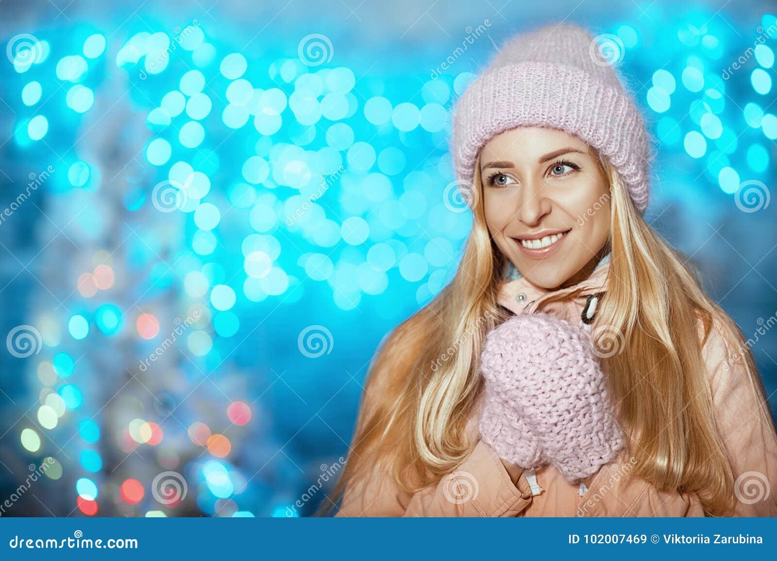 Feliz Natal e ano novo feliz! Retrato da mulher bonita alegre feliz no chapéu e em mitenes feitos malha que fica exterior