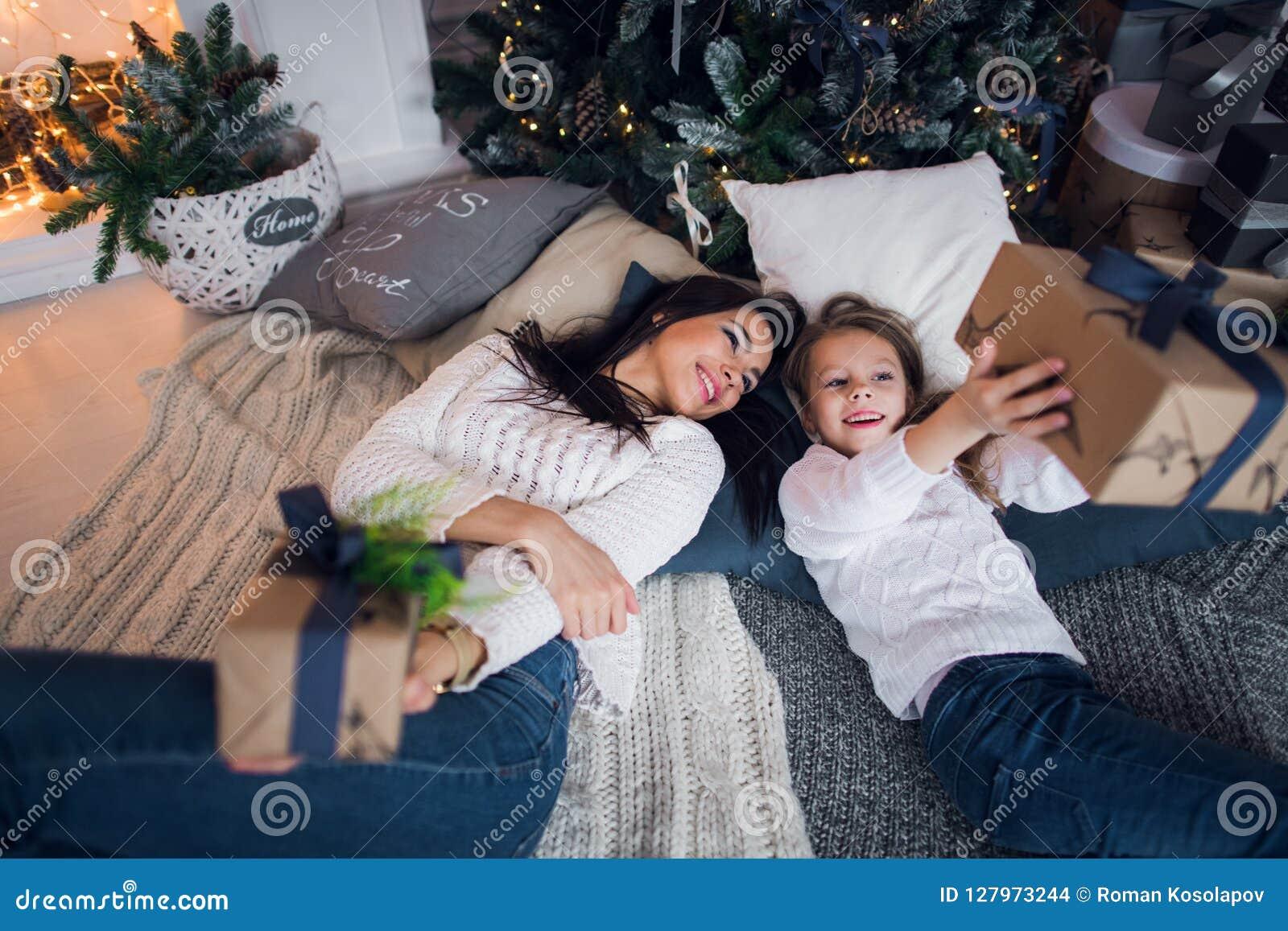 Feliz Natal e boas festas Mamã alegre e sua menina bonito da filha que trocam presentes Pai e criança pequena