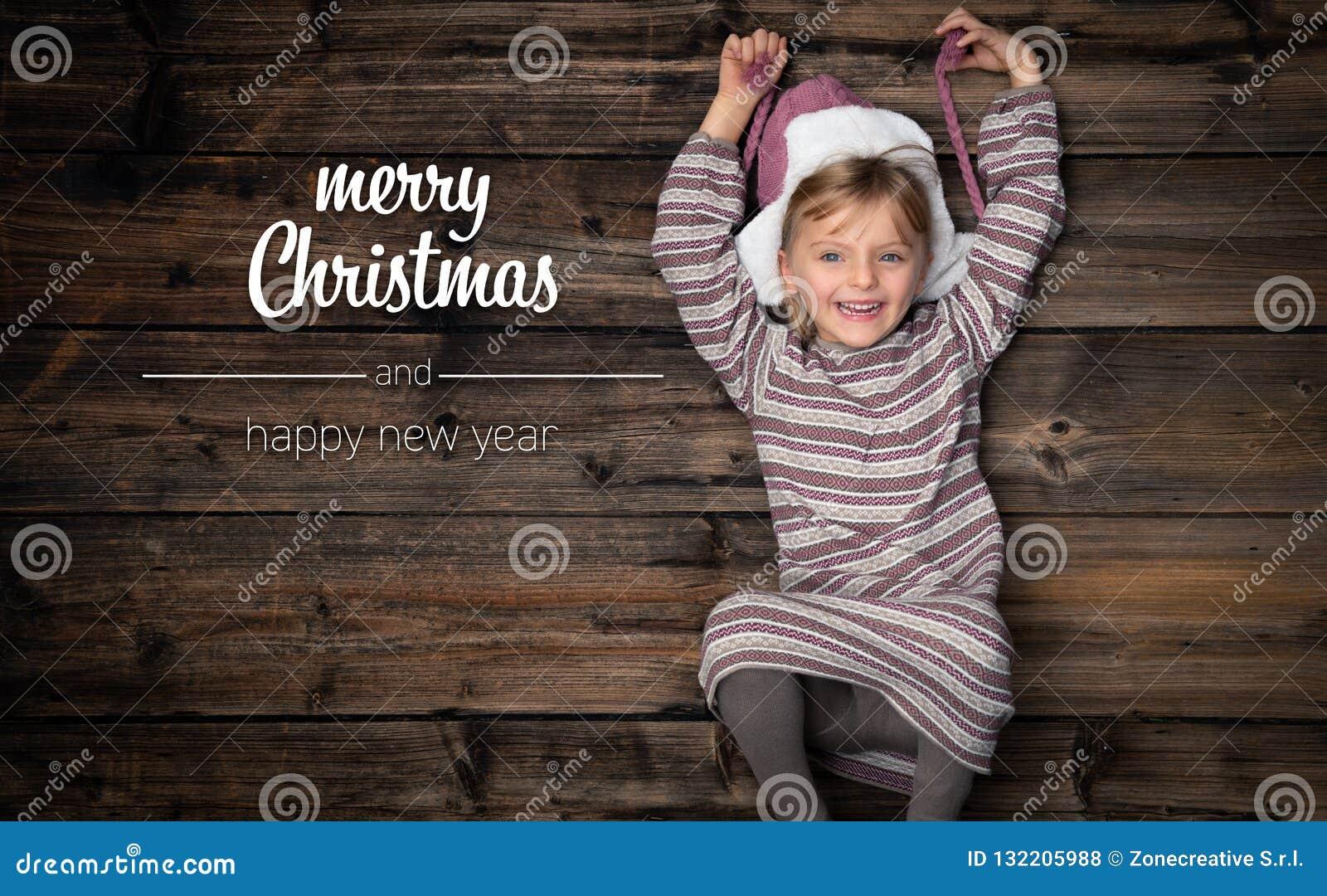 Feliz Natal e cumprimentos do ano novo feliz na madeira escura vertical do vintage da vista superior Menina feliz bonita da crian