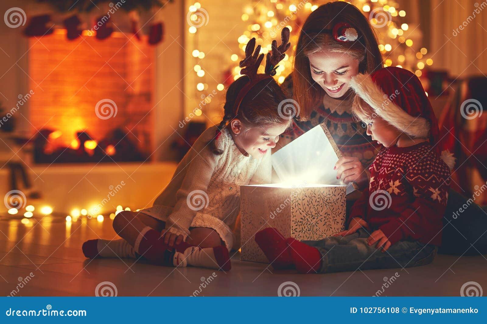 Feliz Natal! mãe e crianças da família com o presente mágico em