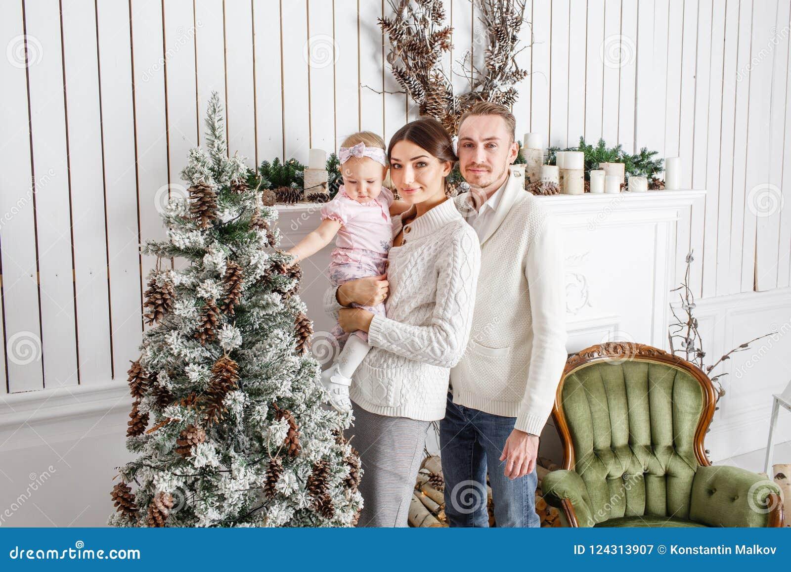 Feliz Navidad de la familia cariñosa y Feliz Año Nuevo Gente bonita alegre Mamá y papá que abrazan a la pequeña hija padres