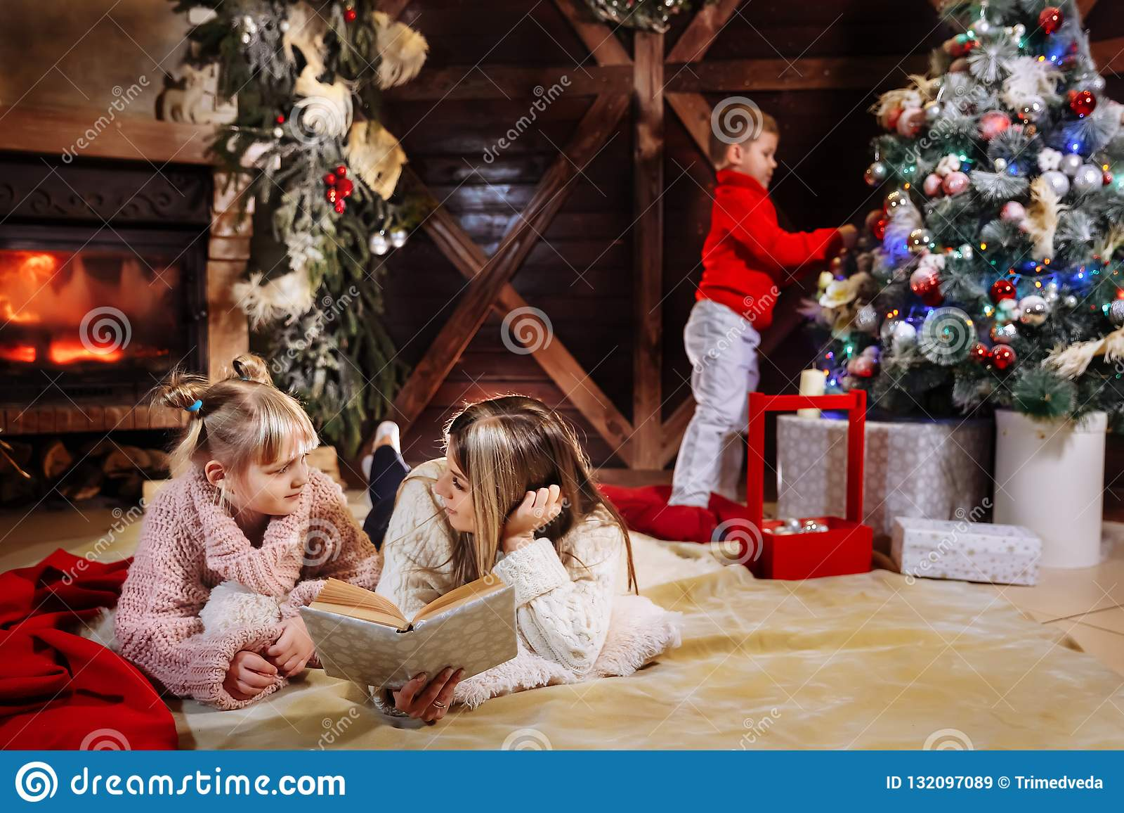 Feliz Navidad y Feliz Año Nuevo Familia hermosa en interior de Navidad Madre joven bonita que lee un libro a ella