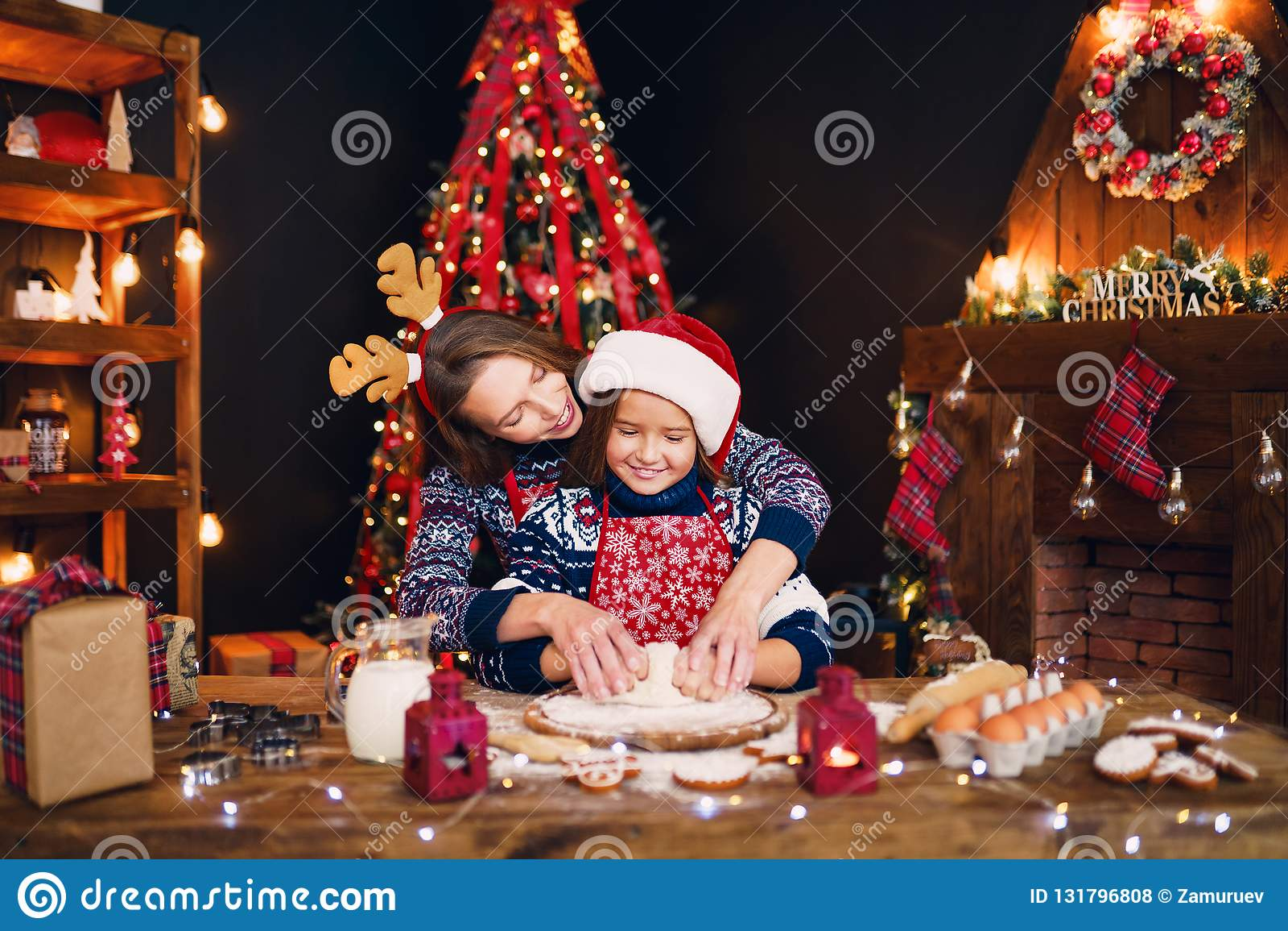 Feliz Navidad y buenas fiestas Madre e hija que cocinan las galletas de la Navidad