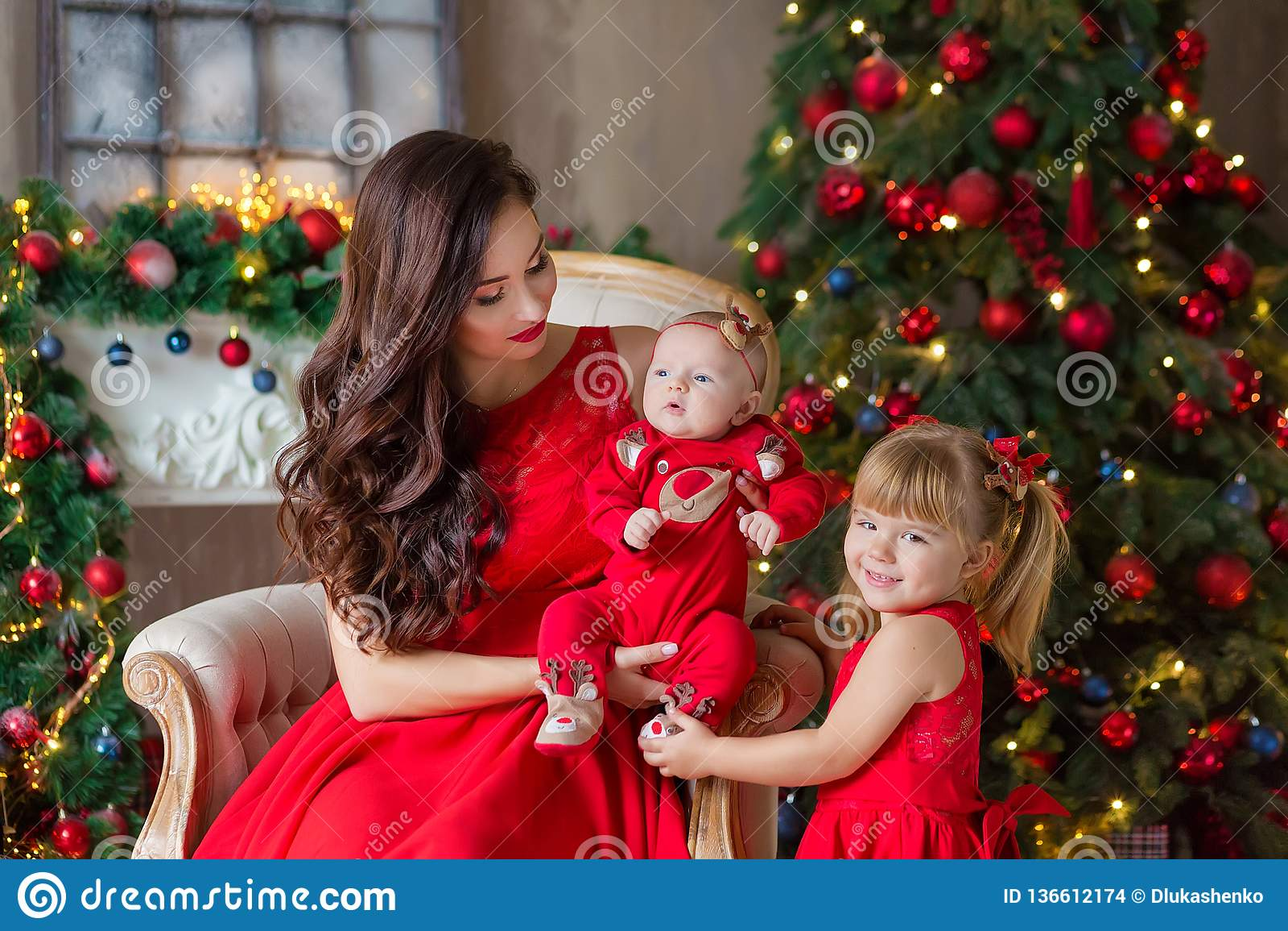 Feliz Navidad y buenas fiestas mamá alegre y su muchacha linda de la hija que intercambian los regalos Padre y poco niño que se d