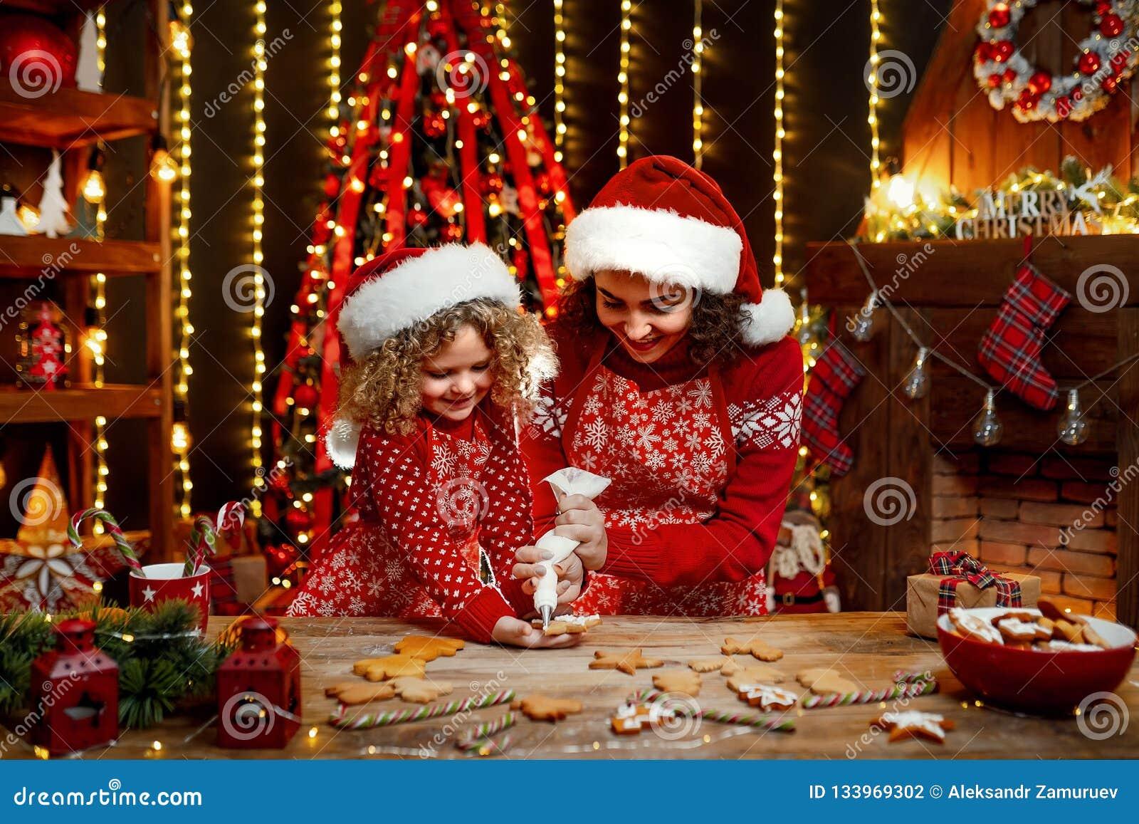 Feliz Navidad y buenas fiestas Niña rizada linda alegre y su más vieja hermana en cocinar de los sombreros de santas
