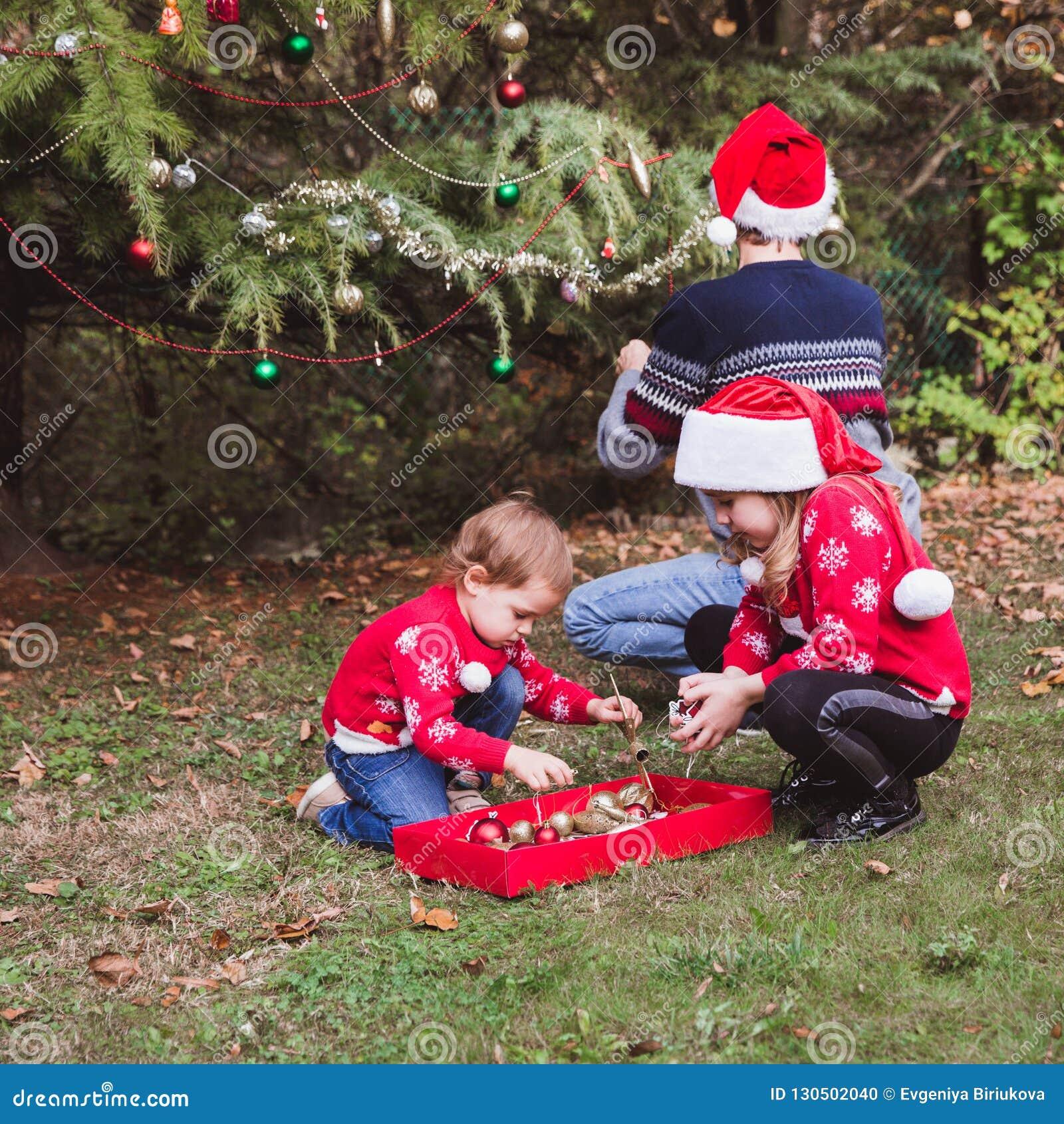 Feliz Navidad y buenas fiestas Padre en sombrero rojo de la Navidad y dos las hijas en suéteres rojos que adornan al ou del árbol