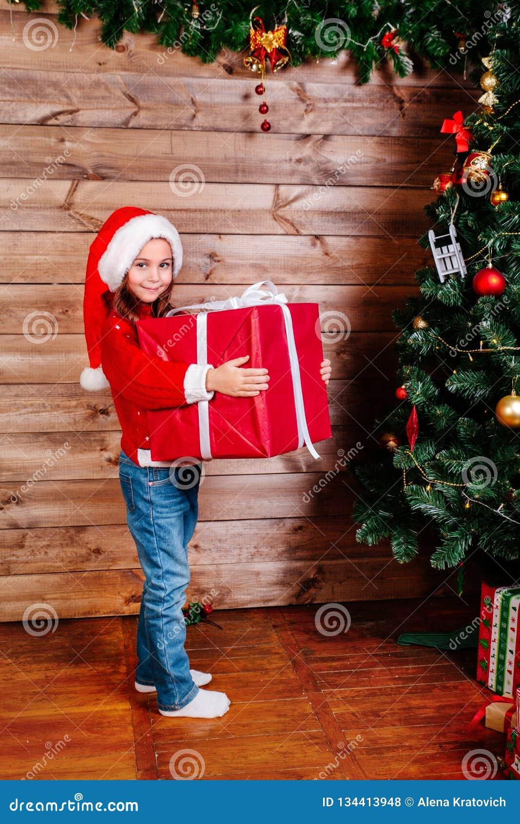 Feliz Navidad y día de fiesta feliz Muchacha linda del pequeño niño con la actual caja de regalo roja grande cerca del árbol inte