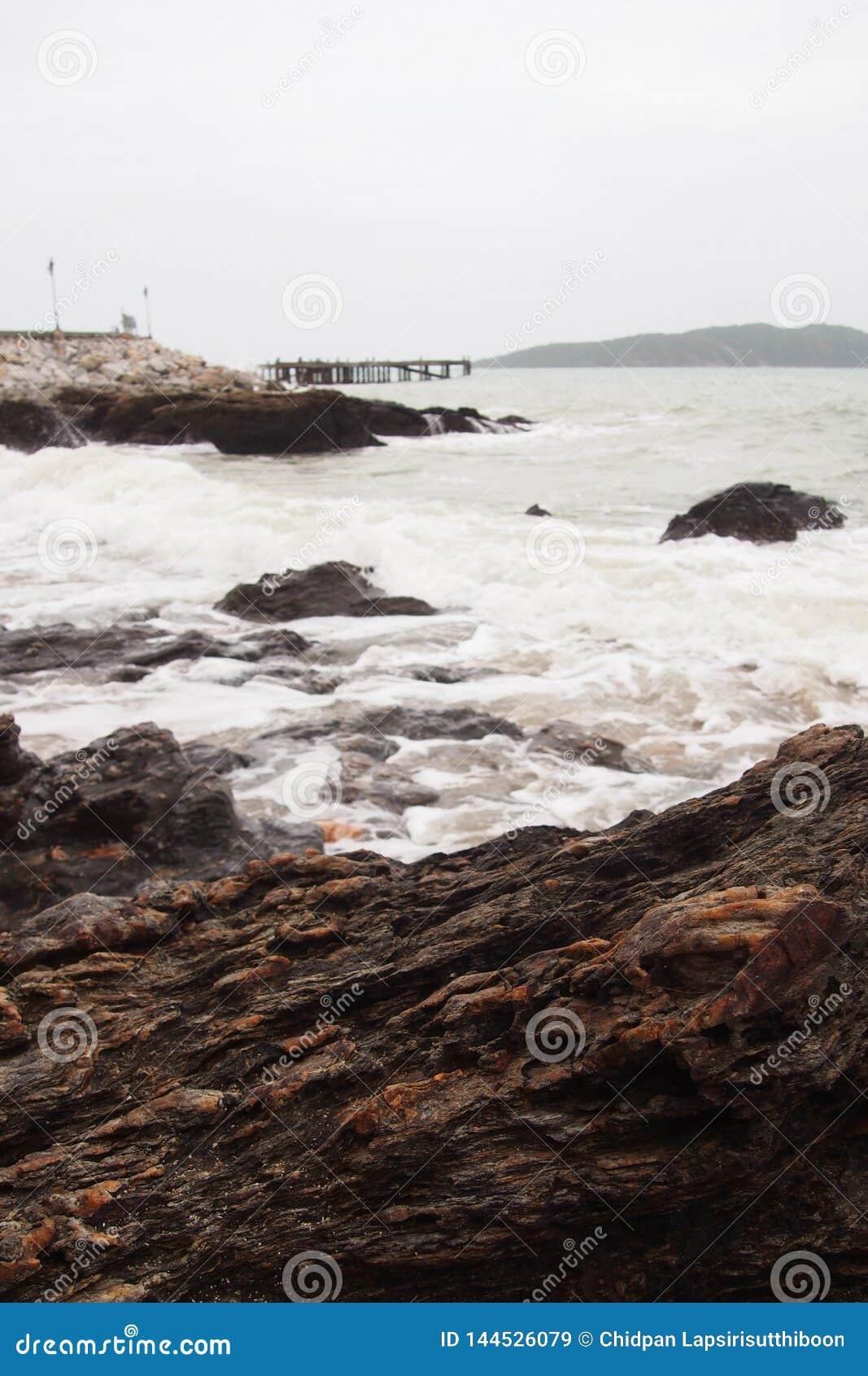 Felsen auf dem Strand durch das Meer, wenn die Brücken in das Meer und in die Laternen ausdehnen, auf einem natürlichen Hintergru