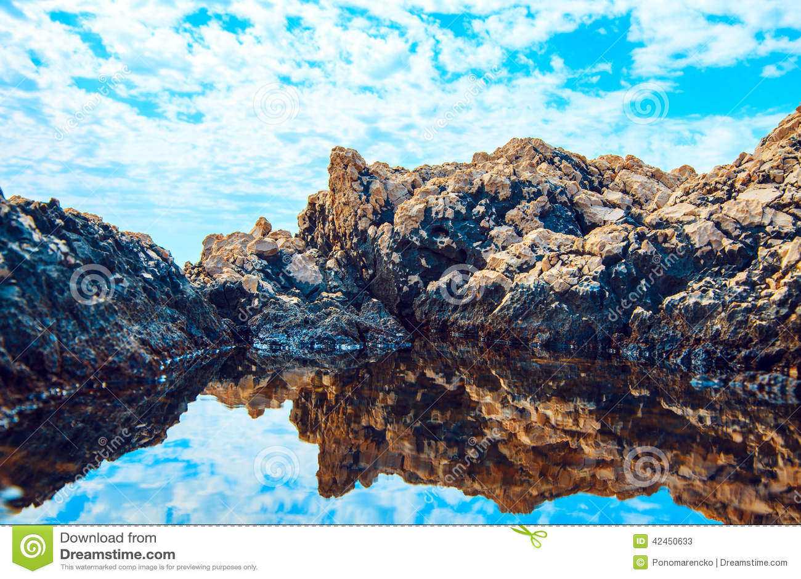 Felsen und ihre Reflexion im Meer
