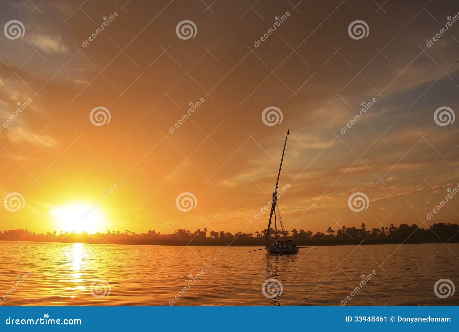 Feluccaboot die op de rivier van nijl bij zonsondergang, luxor, egypte