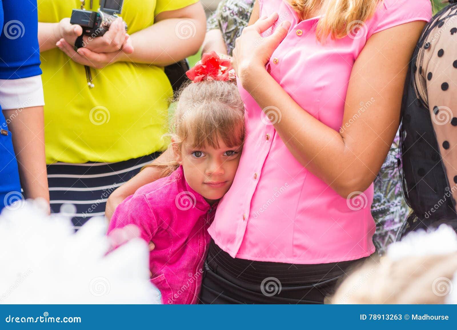 Fem-år flickaanseende i folkmassa och som klamra sig fast intill hennes moder