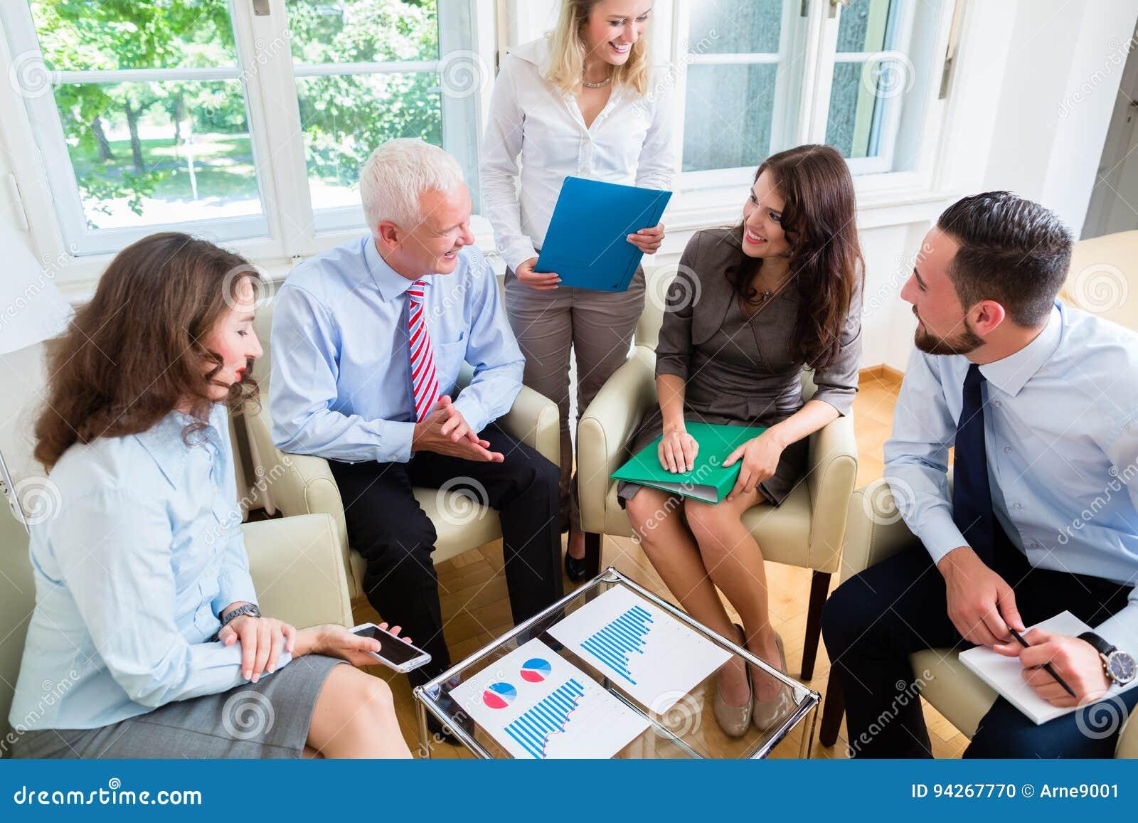 Fem affärspersoner i lagmöte som studerar grafer