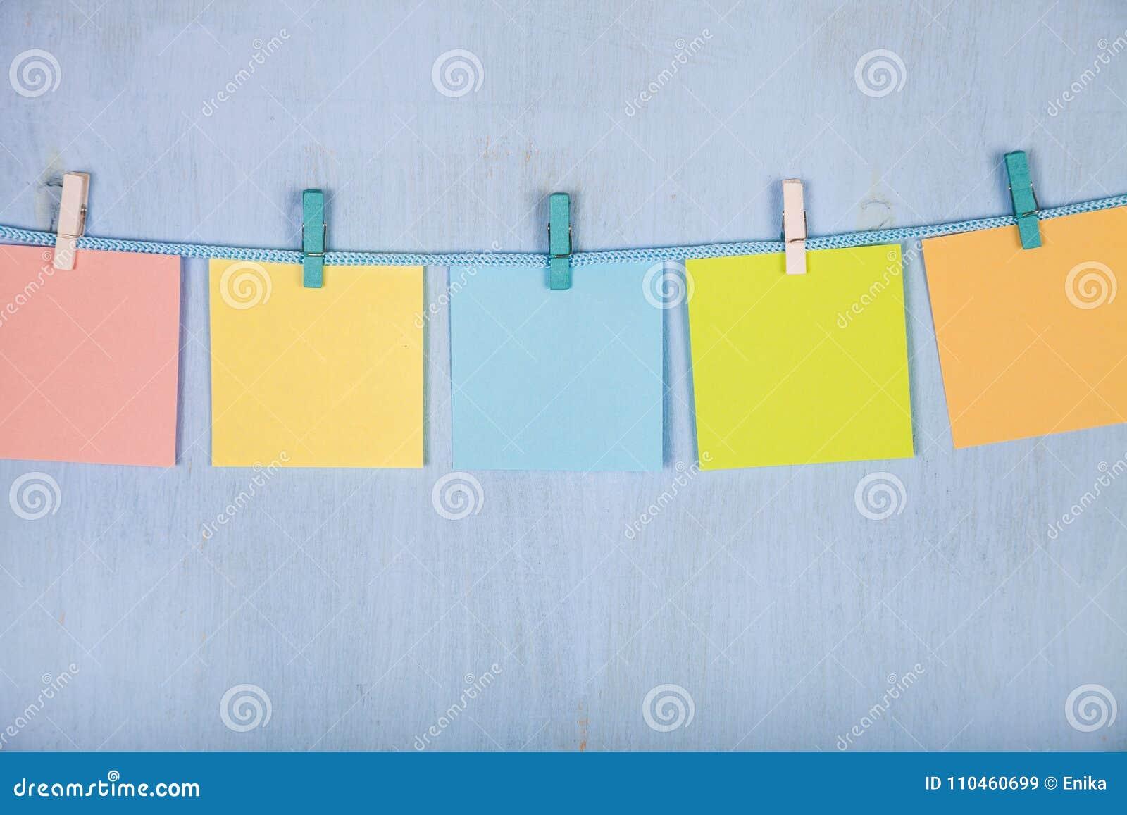 Fem ark av pappershängning på ett rep