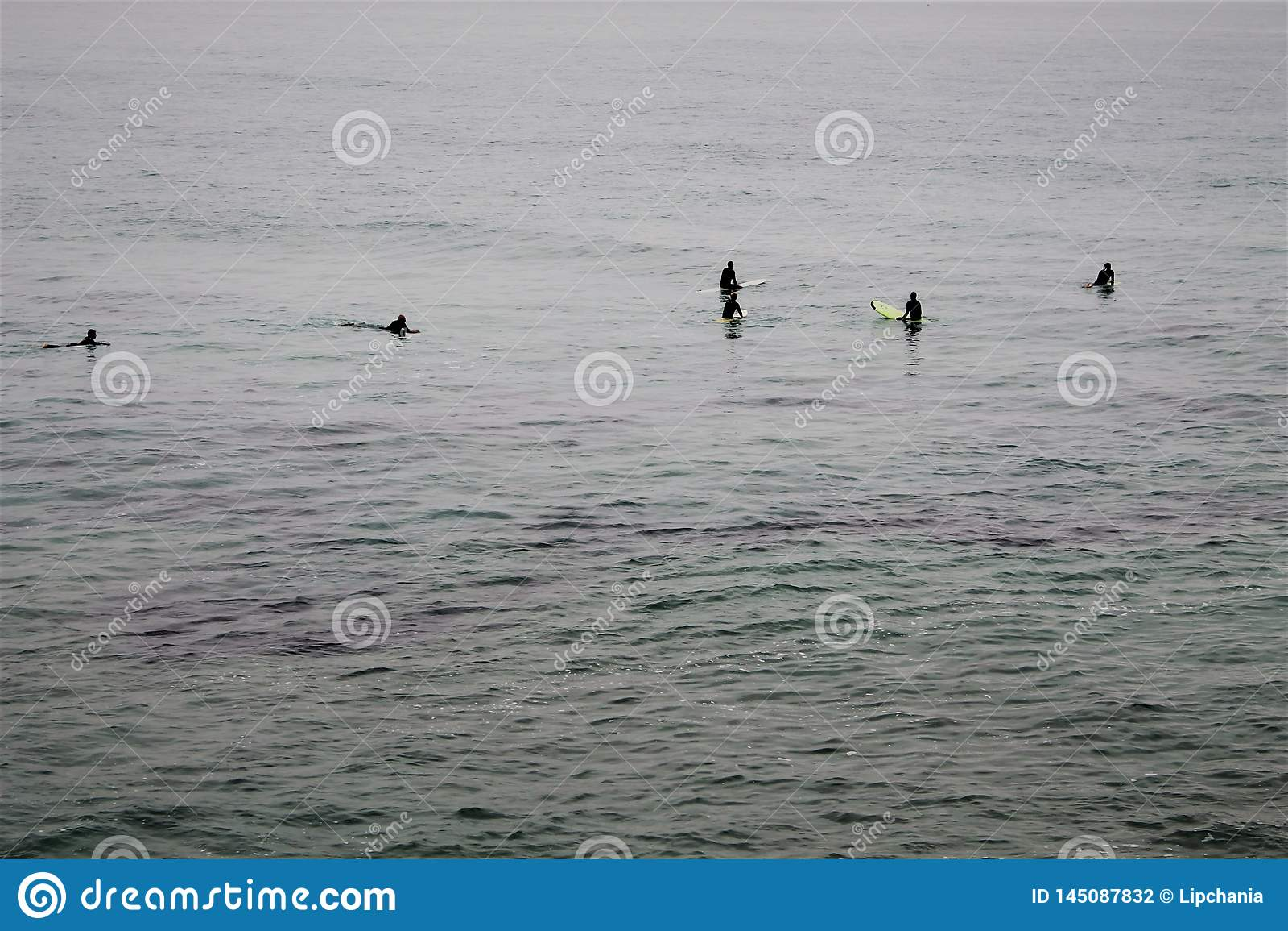 Fem surfare som väntar på en våg