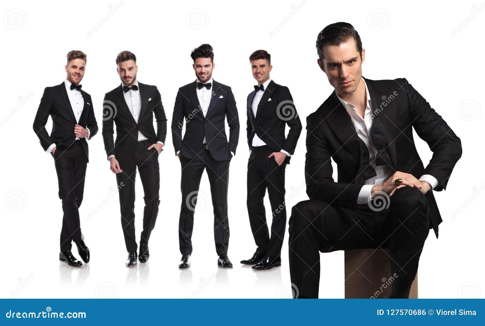 Fem unga män i tuxedoes med ledaren som framme sitter