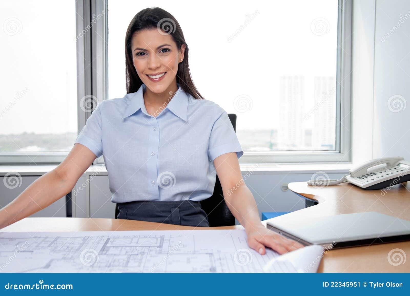 Female architect sitting with blueprints on desk stock for Architecte desl definition