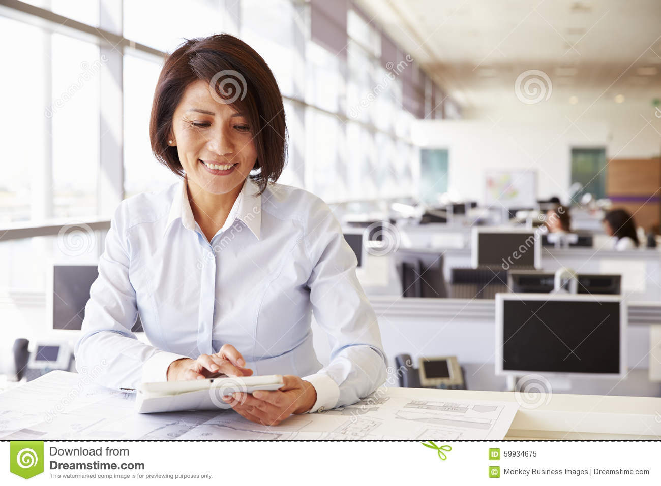Female architect at work in an office using tablet for Architect at work