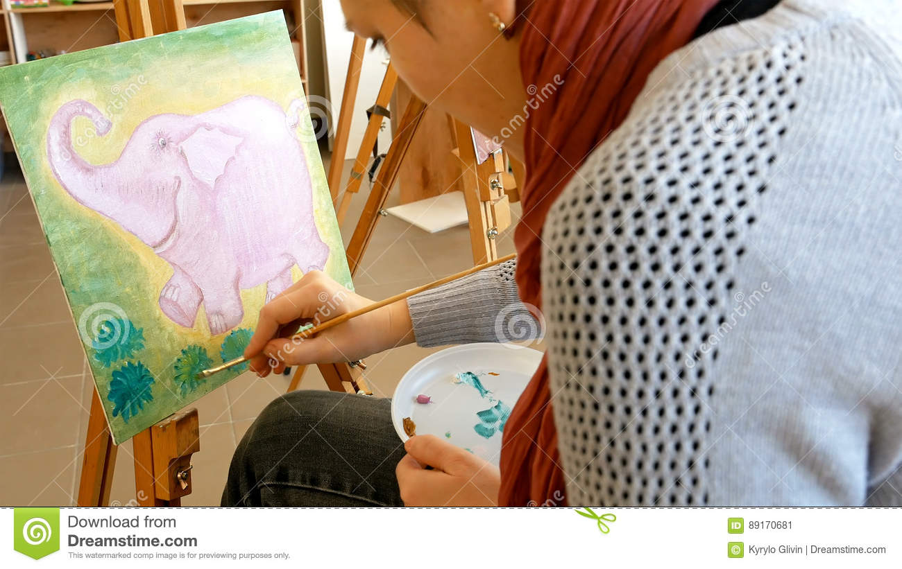 Female artist draws a pencil sketch drawing on canvas easel in art studio student girl learning to draw and paint