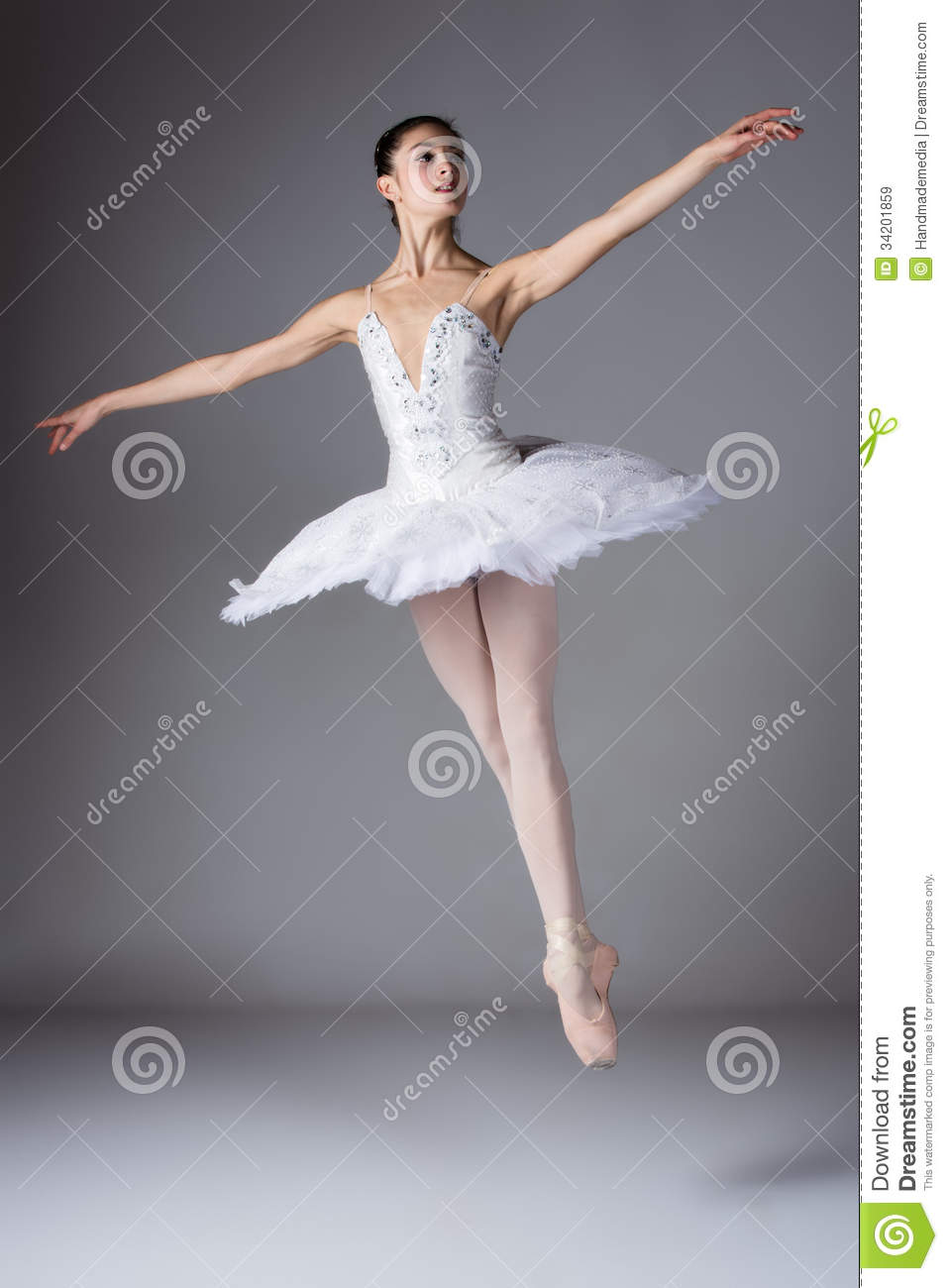 ... grey background. Ballerina is wearing a white tutu and pointe shoes