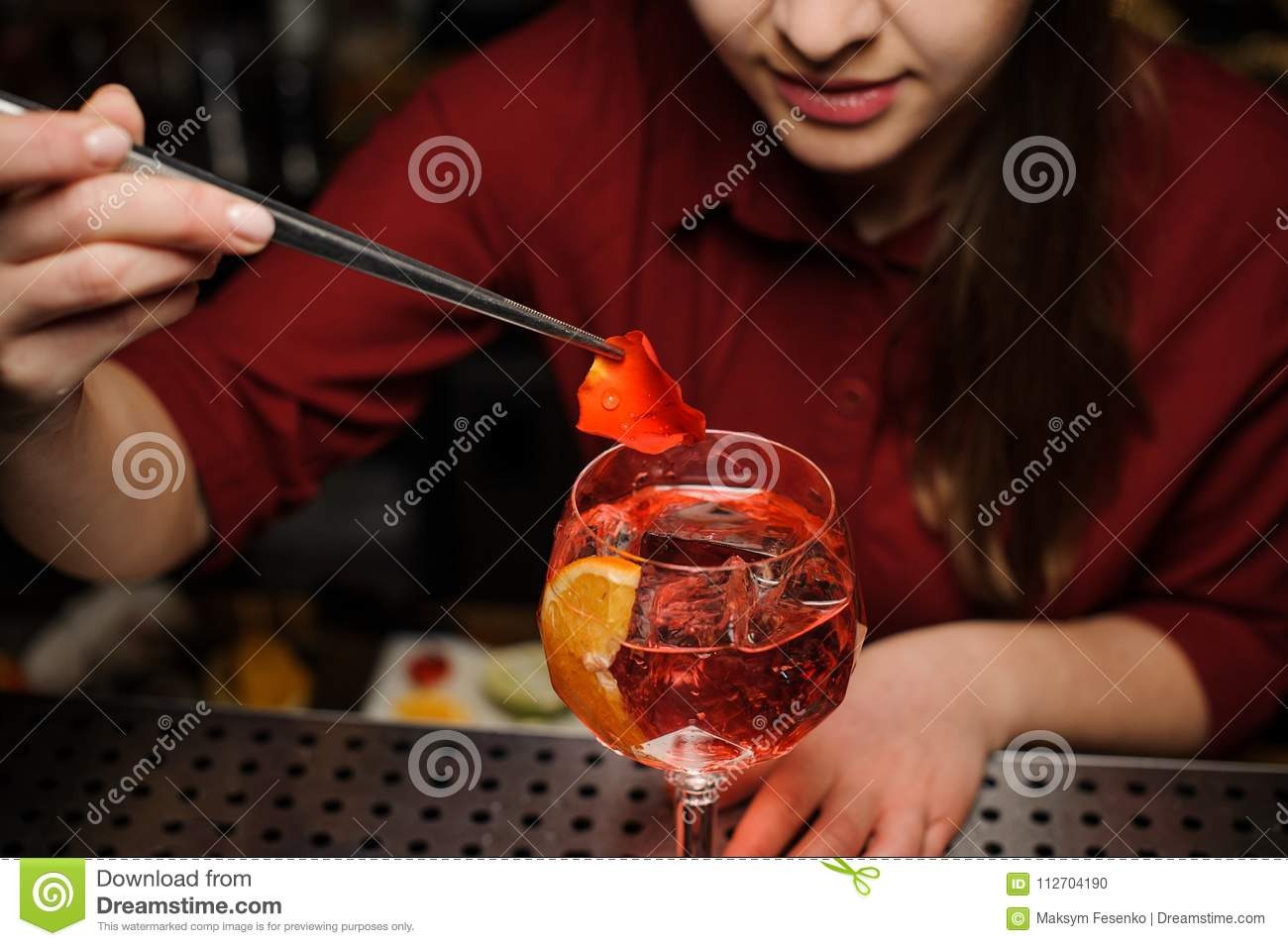 Female Barman Decorating A Glass Of Aperol Syringe Cocktail With