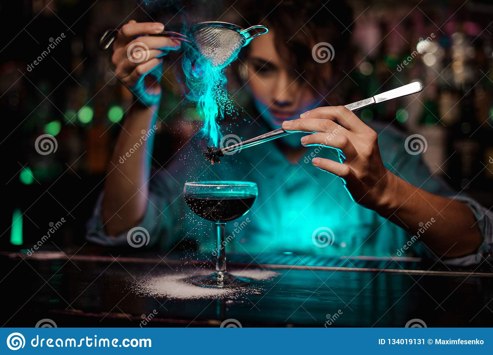 Female bartender pouring on the brown cocktail and on a flamed badian on tweezers a powdered sugar in the green light
