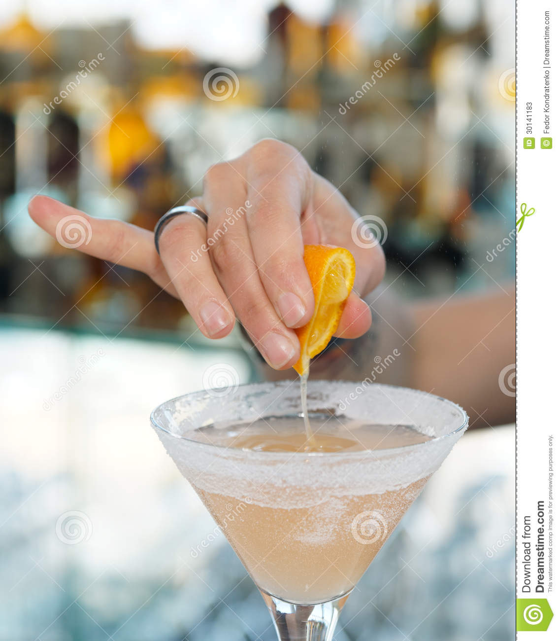 Female bartender is squeezing orange juice into glass