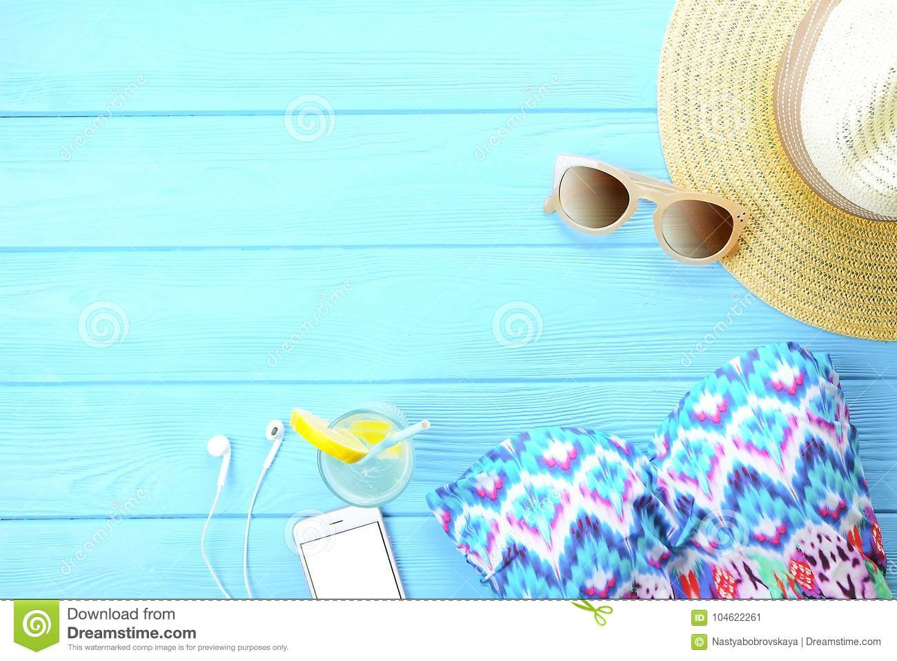 Female beach accessories and phone on wooden background. Top view of trendy woman`s summer holidays accessories. Beach summer fash