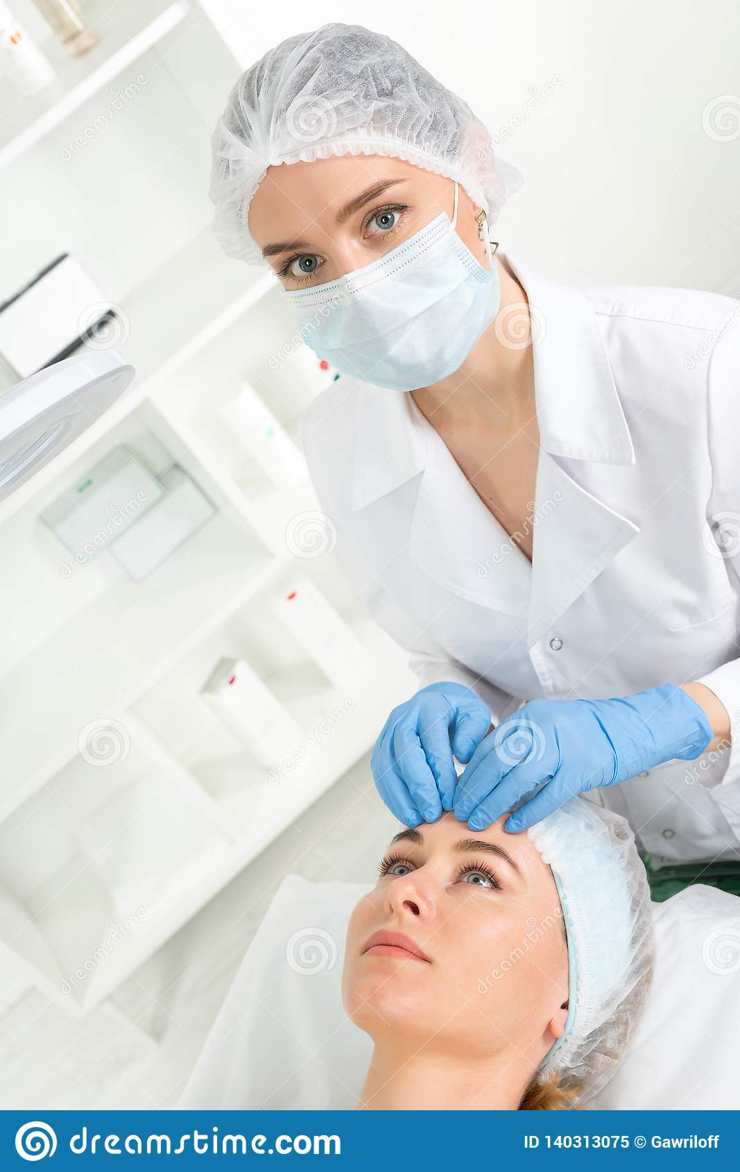 Female beautician doctor with patient in wellness center. Professional cosmetologist make procedure to beautiful girl in