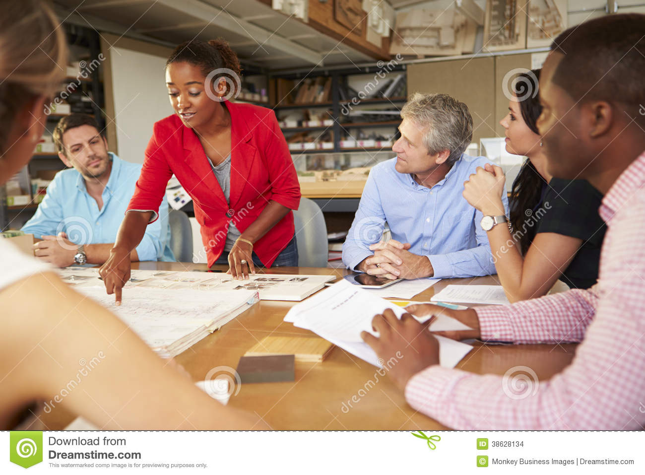 Female boss leading meeting of architects sitting at table for Sitting table designs